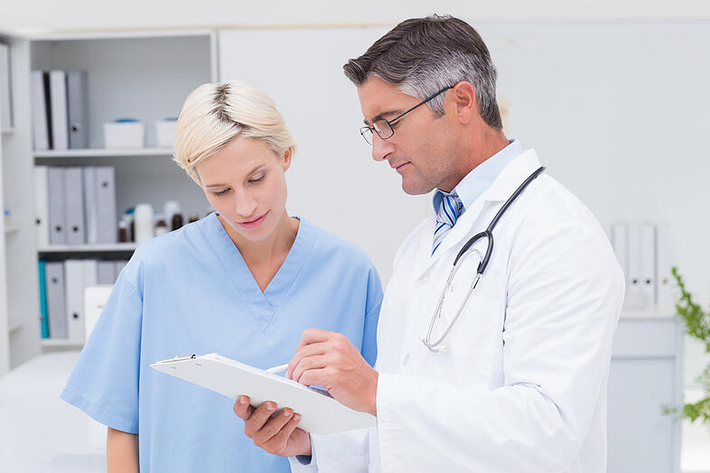 Male doctor and nurse discussing over notes on clipboard in clinic