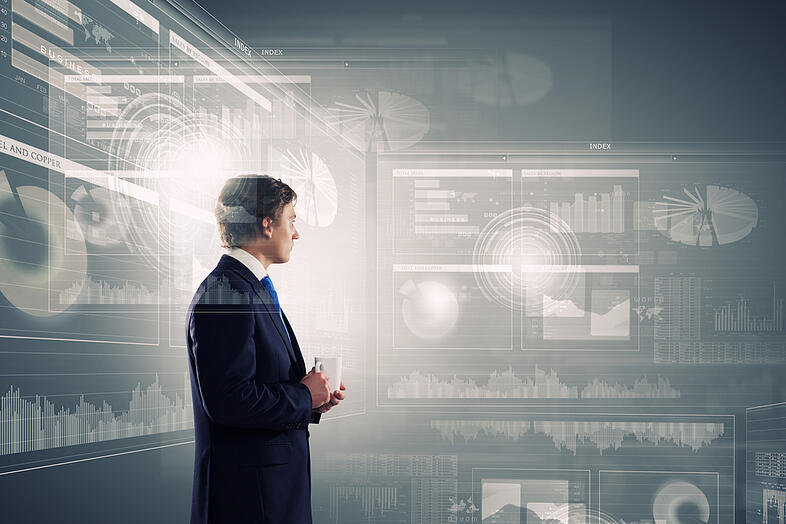 Young businessman with cup in hand looking at media screen