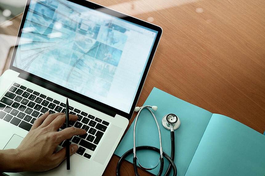 top view of Medicine doctor hand working with modern computer and smart phone on wooden desk as medical concept-1