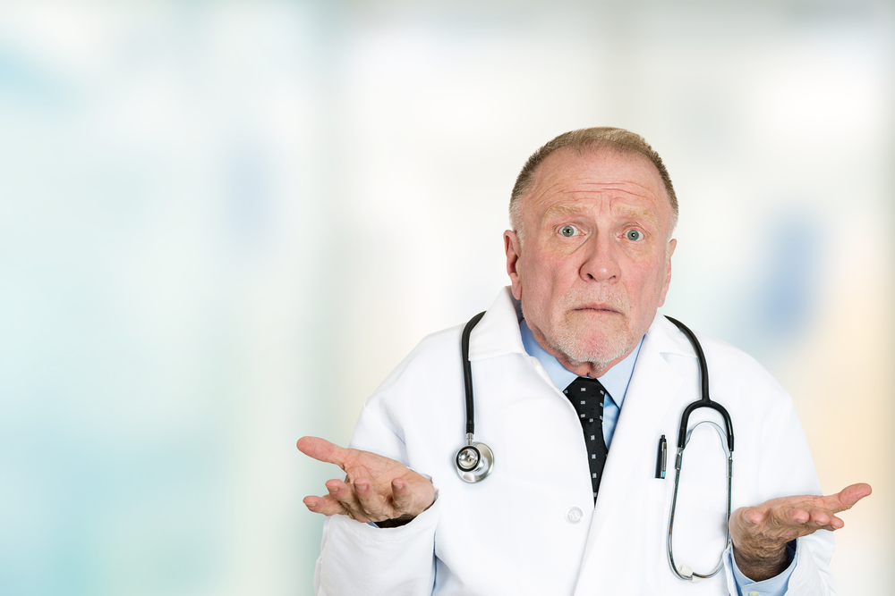 Closeup portrait clueless senior health care professional doctor with stethoscope, has no answer, doesn't know right diagnosis standing in hospital hallway isolated clinic office windows background.